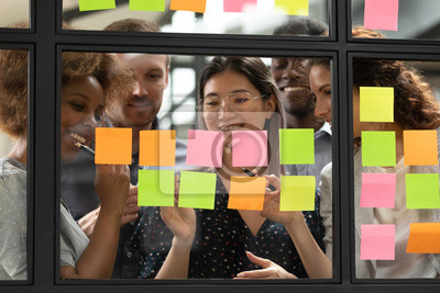 Fototapete Smiling multiethnic colleagues brainstorm using post it stickers