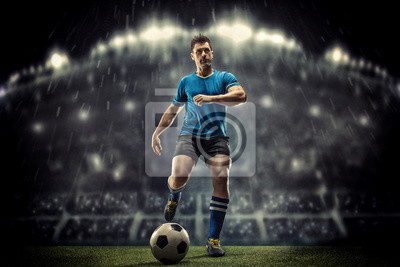 Fototapete Soccer player in action on a dark background