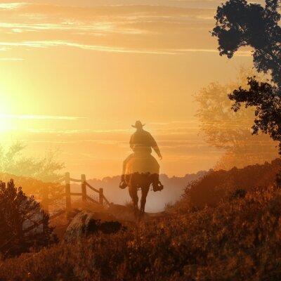 Fototapete Sonnenuntergang-Cowboy. Ein Cowboy reitet in den Sonnenuntergang in transparenten Schichten von orange und gelbe Wolken, einem Zaun und Bäumen.