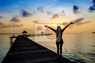 Sorglos Frau in den Sonnenuntergang auf dem Pier.