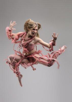 Fototapete Springen gehüllt Frau im Studio über grauem Hintergrund