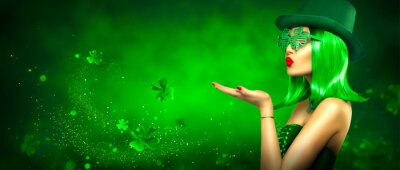 Fototapete St. Patrick's Day leprechaun model girl pointing hand, holding product on green magic background, blowing flying shamrock leaves. Patrick Day pub party, celebrating. Border art design, Widescreen