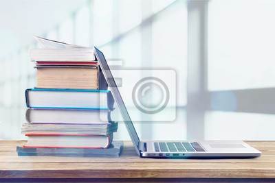 Fototapete Stack of books with laptop on wooden table