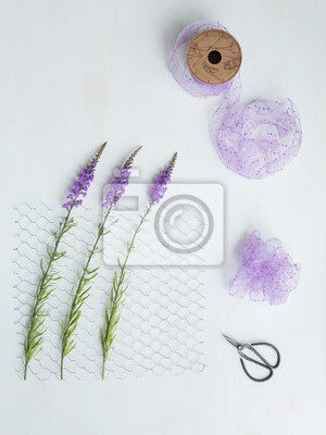 Stilleben mit lila blüten, hühnerdraht, paillettenband und schere ...