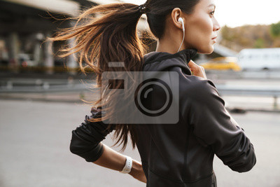 Fototapete Strong fitness woman running outdoors by street.