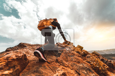 Fototapete Success woman hiker hiking on sunrise mountain peak - Young woman with backpack rise to the mountain top. Discovery Travel Destination Concept
