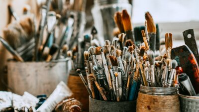 Fototapete Table with brushes and tools in an art workshop. Background.