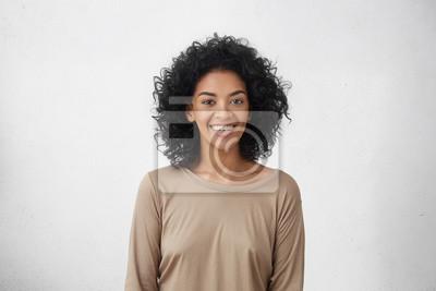 Fototapete Taille bis Porträt von fröhlichen jungen gemischten Rasse weiblich mit lockigen Haaren posiert im Studio mit glücklichen Lächeln. Dunkelhäutige Frau, die beiläufig lächelnd freudig gekleidet war und i