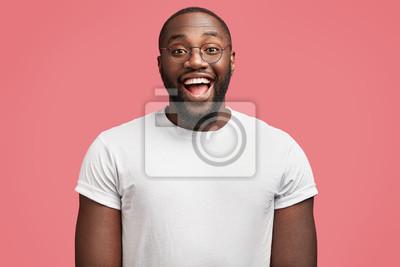 Fototapete Taille herauf Porträt des frohen dunkelhäutigen hübschen männlichen Modells mit glücklichem Ausdruck, trägt die runden Schauspiele und ist in der guten Laune, wie Empfangsbonus für die fleißige Arbeit
