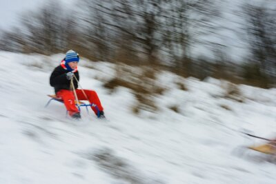 Fototapete the boy descends from the hills in the sled, the movement is blurred 2019
