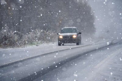 Fototapete The car is driving on a winter road in a blizzard