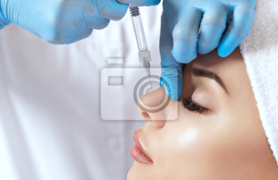 Fototapete The doctor cosmetologist makes prick in the nose to correct the hump of a beautiful woman in a beauty salon. Cosmetology skin care.