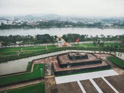 Fototapete The Vietnam flag, waving on top of the stage, in front of the Imperial Palace in Heu, Vietnam. Aerial shot.