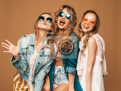 Fototapete Three beautiful smiling hipster girls in trendy summer casual clothes and sunglasses. Sexy carefree women posing near golden wall. Positive models going crazy. Showing tongue