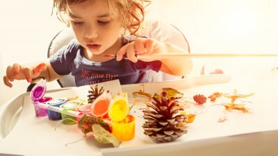 Fototapete Toddler boy is home schooled painting yellow leaves and pine cones in fall with eco friendly paint. Sensorial activity at home.