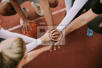 Fototapete Top view of basketball team holding hands over court