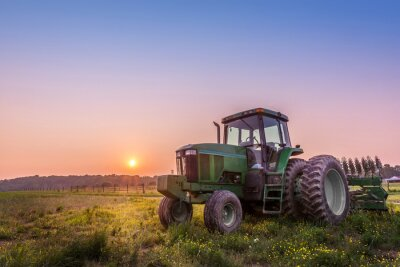 Fototapete Tractor in a field on a Maryland farm at sunset