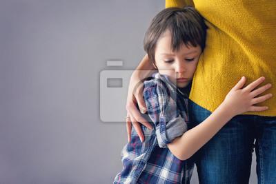 Fototapete Trauriges kleines Kind, Junge, umarmt seine Mutter zu Hause