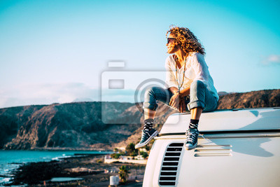 Fototapete Travel concept with independent people enjoyig the outdoor leisure activity and wanderlust life lifestyle - woman sit down on the roof of a old nice vintage camper van
