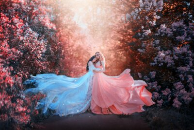 Fototapete two women in long dresses hugging train flies wind. bright fabulous purple colors art retouching processing. Natural cosmetics scented spring flowers tenderness smell perfume. Blonde brunette hair