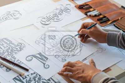Fototapete Typography Calligraphy artist designer drawing sketch writes letting spelled pen brush ink paper table artwork.Workplace design studio.