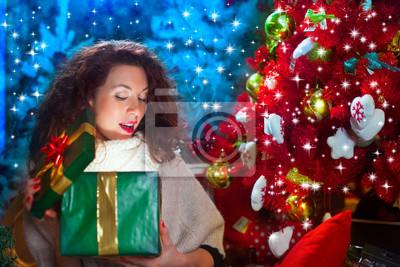 Überraschung freundin, öffnet Geschenk vor dem Weihnachtsbaum