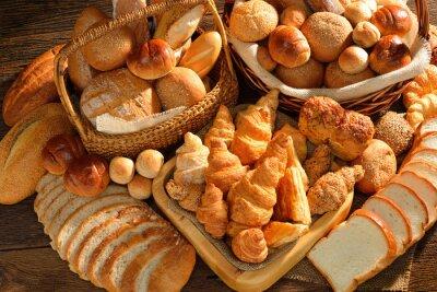 Fototapete Verschiedene Brotsorten im Weidenkorb auf alten Holz-Hintergrund.