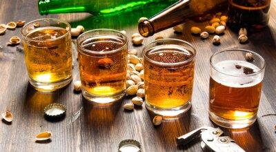 Fototapete Vier Biere mit Pistazien auf einem Holztisch.
