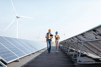 Fototapete View on the rooftop solar power plant with two engineers walking and examining photovoltaic panels. Concept of alternative energy and its service