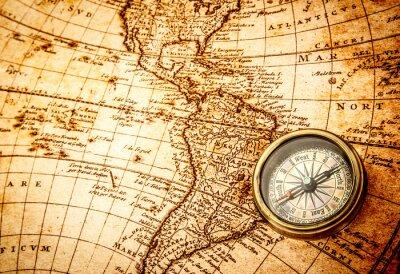 Fototapete Vintage compass lies on an ancient world map.