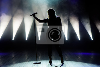 Fototapete Vocalist singing to microphone. Singer in silhouette