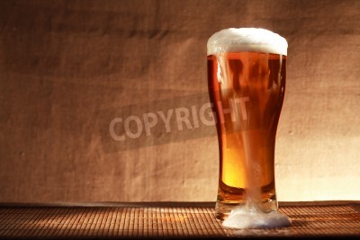 Fototapete Volles Glas Frische Bier mit Schaum auf dem Tisch gegen grauen Leinwand Hintergrund