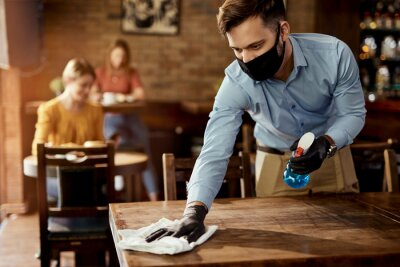 Fototapete Waiter with protective face mask disinfecting tables in a pub.