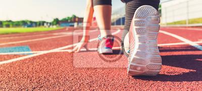 Fototapete Weibliche Athlet auf der Startlinie einer Stadion-Track