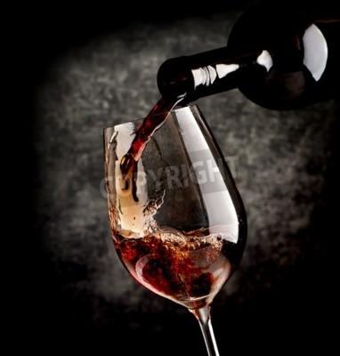 Fototapete Wein gießen in wineglass auf einem schwarzen hintergrund