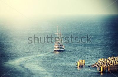 Fototapete Weinlesebild des alten Segelschiffs, das Hafen verlässt.