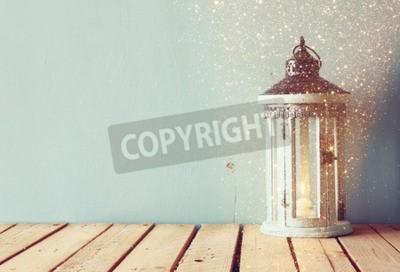 Fototapete Weiße hölzerne Vintage Laterne mit brennenden Kerze und Baum Zweige auf Holztisch. Retro-gefiltertes Bild mit Glitzer-Overlay