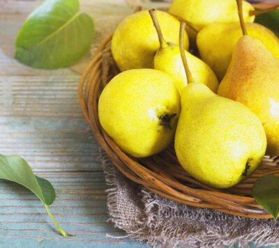 Fototapete Wicker basket of ripe pears, close up
