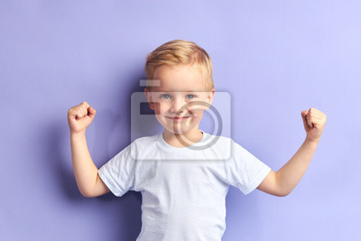 Fototapete Winner kid isolated over purple background, show how powerful he is. Isolated over purple background