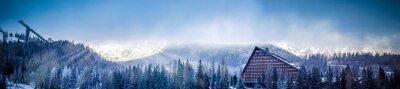 Fototapete Winter-Panoramablick auf Berg mit einem Hotel und Skisprung-Plattform, Sonne mit Wolken bedeckt