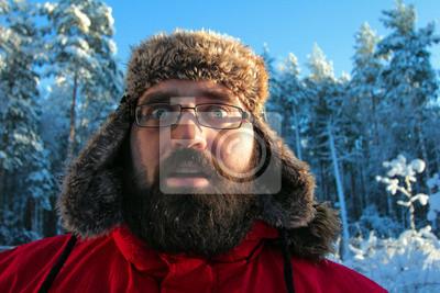 Winterportrait des bärtigen Mann in russische Pelzmütze