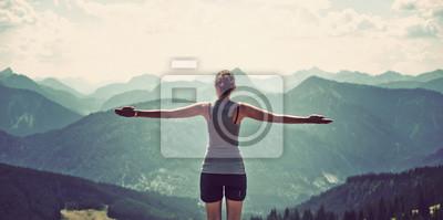 Fototapete Woman celebrating nature and reaching the summit