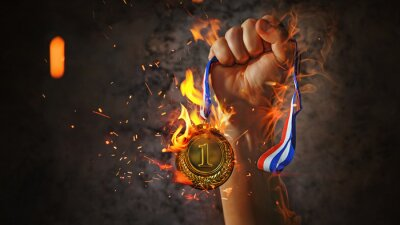 Fototapete woman hand raised, holding gold medal in the fire. award and victory concept