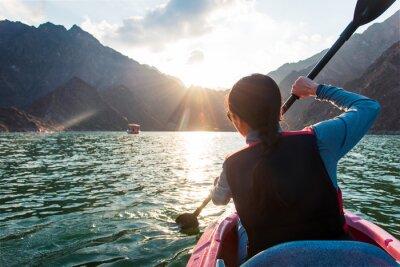 Fototapete Woman kayaking in Hatta lake in Dubai at sunset