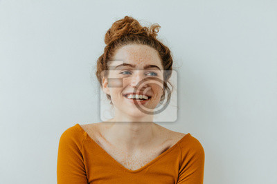 Fototapete Woman portrait. Happiness. Beautiful blue eyed girl with freckles is looking away and laughing, on a white background