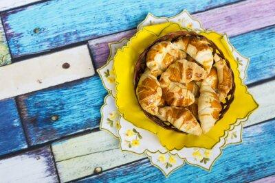 Fototapete Самодельные круассаны в плетеной корзинке на желтой салфетке с цветочным узором на старом / вытертом полу