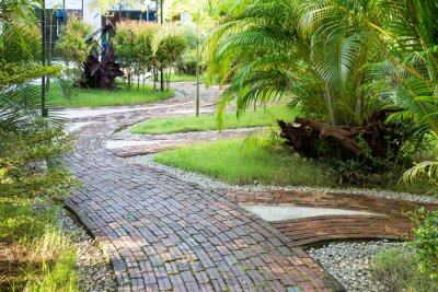 Fototapete Garden walking way made of clay brick in the pleasant morning light
