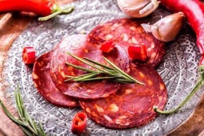 Fototapete Wurst Chorizo. Spanische traditionelle Chorizo Wurst, mit frischen Kräutern, Knoblauch, Pfeffer und Chilischoten. Traditionelle Küche.