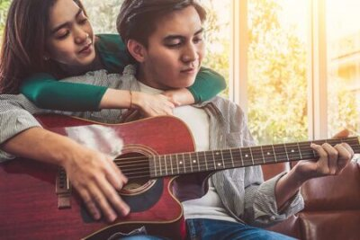 Fototapete Young Asian Couple Plays Guitar and Sing Song in Living Room at Home Together. Music and Lifestyle concept.