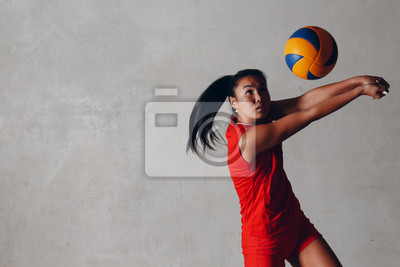 Fototapete Young Asian woman volleyball player in red uniform takes ball